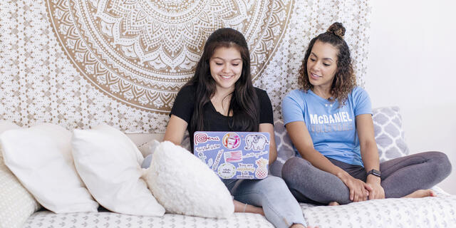 Students on computer in residence hall room.
