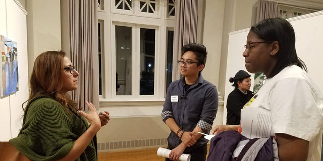 Students talk to an alum at a networking event.