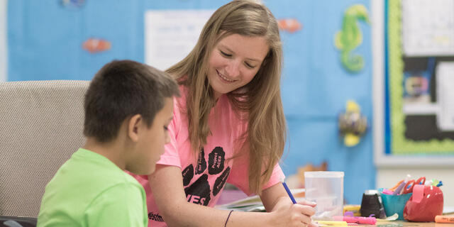Student teaching one-on-one in elementary school setting.